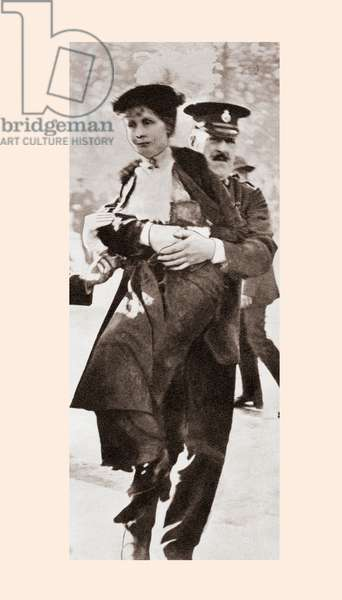 Emmeline Pankhurst, born Emmeline Goulden, 1858 – 1928.  British political activist and leader of the British suffragette movement.  Seen here being arrested and bodily carried away from a demonstration outside Buckingham Palace in 1914.   From The Story of 25 Eventful Years in Pictures published 1935