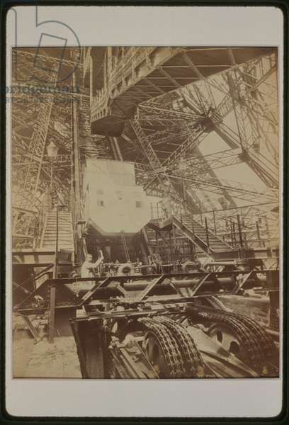 Eiffel Tower machinery with man beside wheel that raises ele