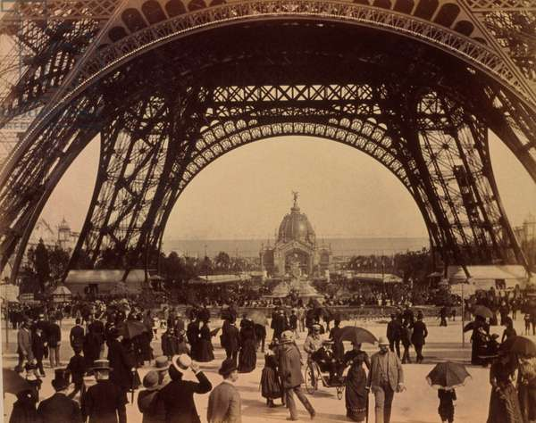 Crowd of people walking under the base of Eiffel Tower, view