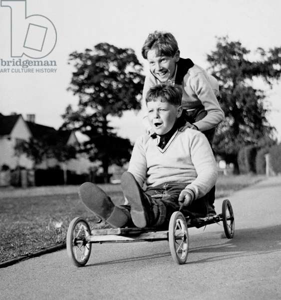 Two boys on a home-made go-kart