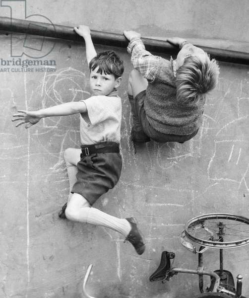 Two boys climbing wall on a Balham street, SW London