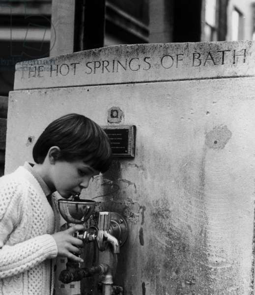 Boy at hot springs water fountain, Bath