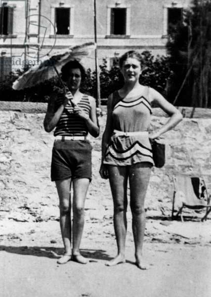Lady holding a sunshade with friend on the beach