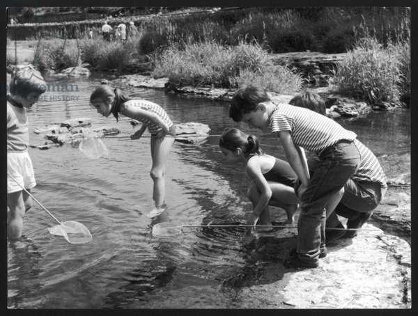 CHILDREN FISH IN STREAM