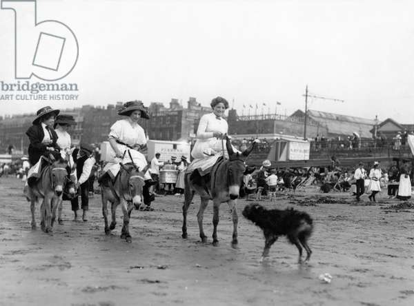 Holidaymakers riding donkeys on a beach