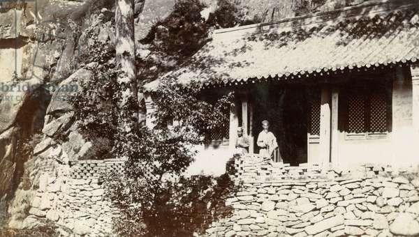 Elderly Chinese couple outside house