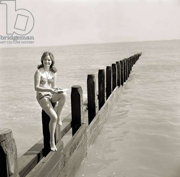Butlins Holiday Camp at Bognor A young woman wearing a bikini sitting, a barrier, June 1962 (b/w photo)