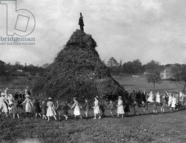 One of the biggest bonfires to be burnt is the huge 50 ft. high pyre erected in to ground of the Aldersbrook Children's Homes, Wanstead, London. This pyre took a month to build and is the remnants of all the waste branches and rubbish that local firms and people wish to dispose of. These children, toddlers, and those up to the age of 15, watch this huge nobfire burn and are given a display of fireworks bought from donations and collections from well wishers. The toddlers are not told about Guy Fawkes because many of them are very upset when they see him burning. They are told it is a bag of straw. Before the bonfire is lit the children and nursesplay ring-a-roses round the base which is 50 yards round. 4th November 1948 (b/w photo)