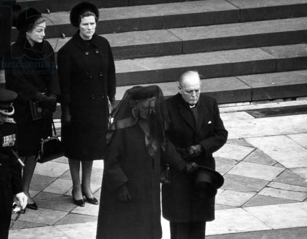 The funeral of Sir Winston Churchill. After the state funeral service in St Paul's Cathedral, the coffin is taken to Bladon Church near his birthplace, Blenheim Palace, Oxfordshire, where Sir Winston will be buried in accordance with his own wish. Pictured, after the funeral service Lady Churchill watches as her husband's coffin is loaded onto the gun-carriage at the foot of St Paul's Cathedral steps. With her is her son Randolph and behind them her daughters Sarah (Lady Audley) on left and Mary (Mrs Chrstopher Soames). 30th January 1965 (b/w photo)