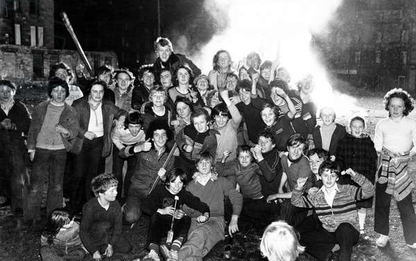 A blazing row ended happily for these children. It started when police told them their Guy Fawkes Night bonfire was too big. But as police reinforcements arrived, the youngsters, backed by their parents, stood firm. Eventually, after a sergeant had calmed everything down, the police relented - and the bonfire was soon blazing away merrily. Dale Street, Bridgeton, Glasgow, Scotland. 5th November 1978 (b/w photo)