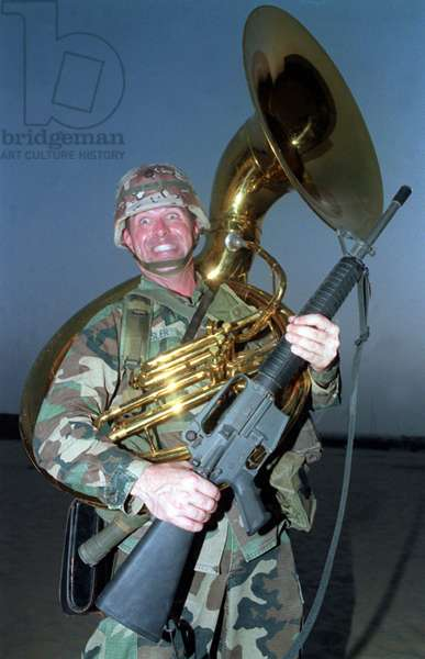 American soldier holding machine gun and wearing a sousaphone, 1991 (photo)
