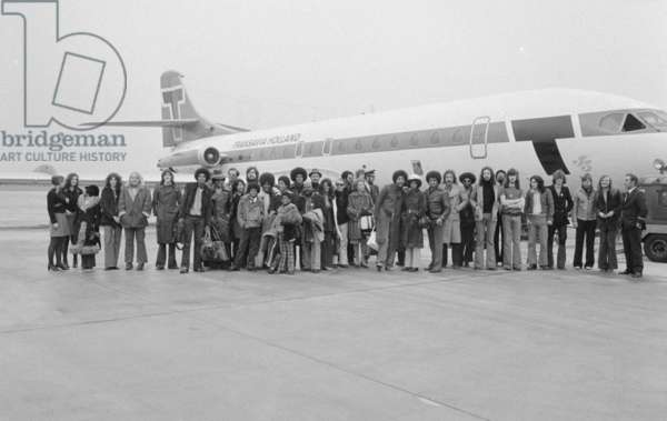 The Jackson Five pop group stand beside their plane as they arrive at London airport accompanied by memebrs of their family and their crew, 7th November 1972 (b/w photo)
