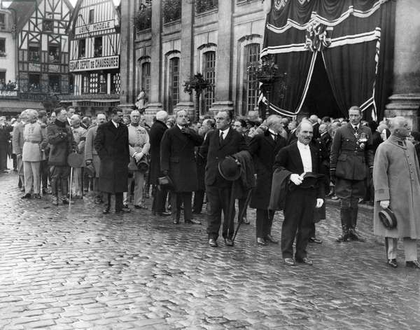 elebrities including Air Chief Marshall Sir John Salmen (extreme right) line up outside the Beauvais Town Hall in France for the funeral procession of the victims of the R101 airship tragedy. October 1930