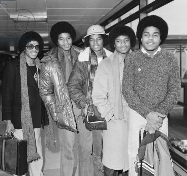 Members of The Jackson Five pop group make their way through the arrivals hall as they arrive in London for a UK tour, 4th February 1979 (b/w photo)
