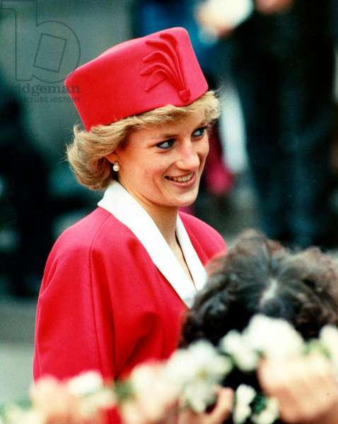 Princess Diana on a walkabout during visit wearing red suit and red pillbox hat looking coy, May 1989 (photo)