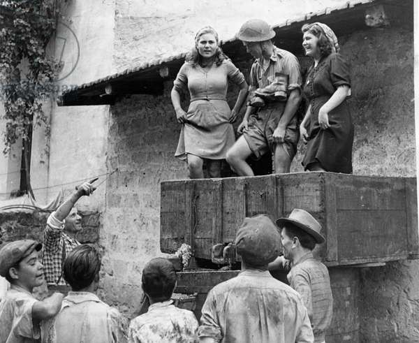 A British soldier helping the local villagers with the winepress after the Allied army invasion and liberation of Southern Italy and Sicily November 1943 (b/w photo)