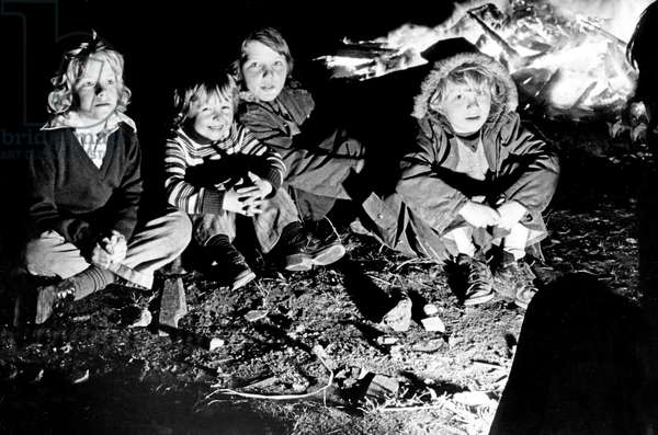 The thrills of Guy Fawkes night are reflected in the faces of these youngsters as they gathered round their bonfire in Premier Street, Everton, Merseyside last night. 5th November 1974 (b/w photo)