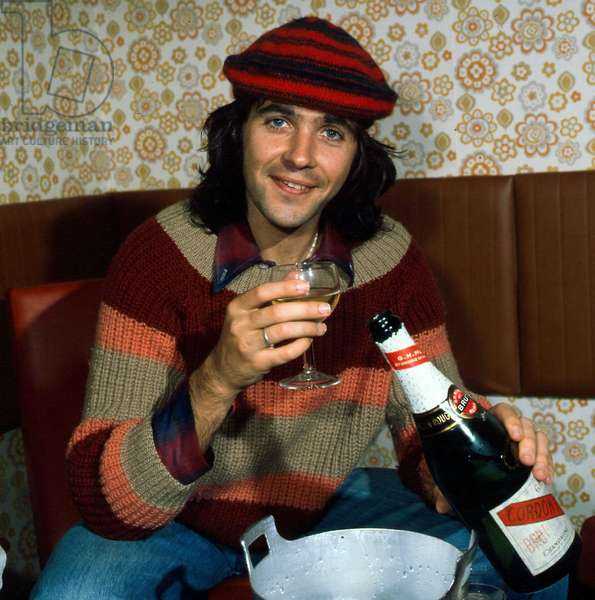 A portrait of David Essex, taken in Scotland, wearing a multicoloured pullover and a tammy hat, holding a bottle of Champagne, 24th September 1975 (photo)