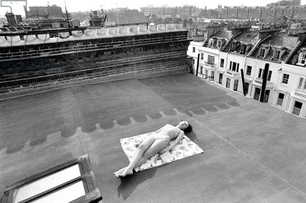 A model wearing a bikini as she sunbathes on a rooftop on Kings Road in Chelsea, London, April 1975 (b/w photo)