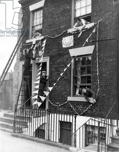 Queen Elizabeth II, Princess Elizabeth - Coronation - Residents from Scotswood Road in Newcastle decorating it in preparation for the coronation, 1950 (b/w photo)