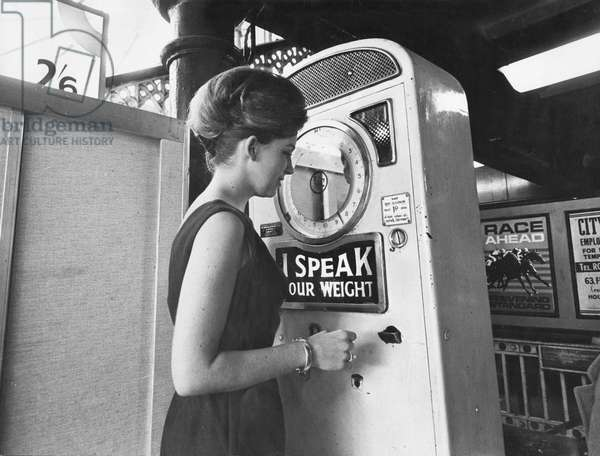 Every year the British public pop a million pennies into machines designed to speak, dial or stamp their true weight. Do they get their money's worth? To find out, the Sunday Mirror conducted an experiment with machines used by people from all over the country at London railway termini. Our picture shows Carolyn Martin at Liverpool Street Station were the machine said 8 stone 6lb, the dial showed 8st 7lb. 4th April 1965 (b/w photo)