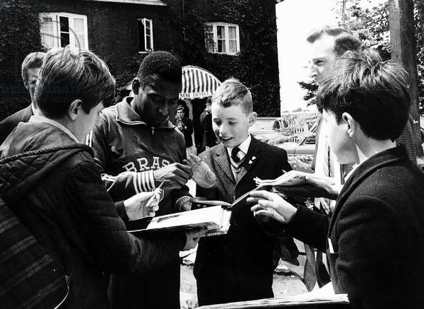 Brazilian football star Pele signing autographs for fans outsode his hotel in Lymm, Cheshire during the 1966 World Cup tournament in England. July 1966 (photo)