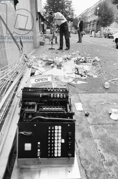 A Co-op worker sweeping up debris after riots in Notting Hill, 1976 (b/w photo)