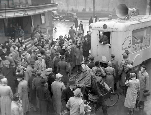 People gather around the Ministry of Information van parked outside the Coventry Hippodrome Theatre in Hales Street to hear announcements and advice, 18th November 1940 (b/w photo)