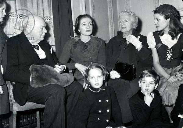 "Grandpa Sir Winston-hand in muff-presides over a family group at London's Scala Theatre, where they saw ""Peter Pan"". Peter Pan was played by daughter Sarah Churchill-who sits between Sir Winston and Lady Churchill. Arabella, 9, daughter of Mr and Mrs Randolph Churchill stands next to her grandfather. Seated on the floor are (l to r) Emma,9, and Jeremy, 6. Sitting on the left of Lady Churchill is Julia Lockwood who plays Wendy in Peter Pan.Sir Winston, 84 kept his beaver muff on his lap throughout the performance and receiveed a tremendous standing ovation from the audience. December 1958 (b/w photo)"