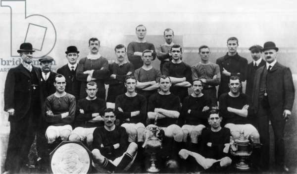 Manchester United, winners of the Football League Division One, FA Charity Shield and Manchester Senior Cup in 1908. Pictured Back row left to right: Alex Downie and Herbert Burgess.  Third Row l-r: Director J Taylor, Assistant trainer J,Nuttall, Director Harry Stafford, Herbert Broomfield, George Stacey, Dick Duckworth, Richard Holden, Alex Bell, Harry Moger, trainer Fred Bacon and Secretary Manager J. E. Magnall.  Second Row: L-R: John Picken, James Bannister, Jimmy Turnbull, captain Charlie Roberts, Harold Halse, Sandy Turnbull. Front two: L-R: Billy Meredith and George Wall .