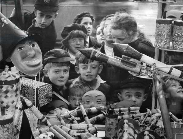 Customs Guy Fawkes Day: A jumble of small faces peer at a pile of very big bangers. You can just imagine the fun these Caversham children will have on Bonfire Night. October 1959 (b/w photo)