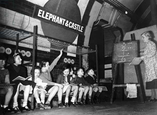 Miss A. Potter teaching children in a maths lesson in Elephant and Castle Underground Station as they shelter during an air raid over London, March 1941 (b/w photo)