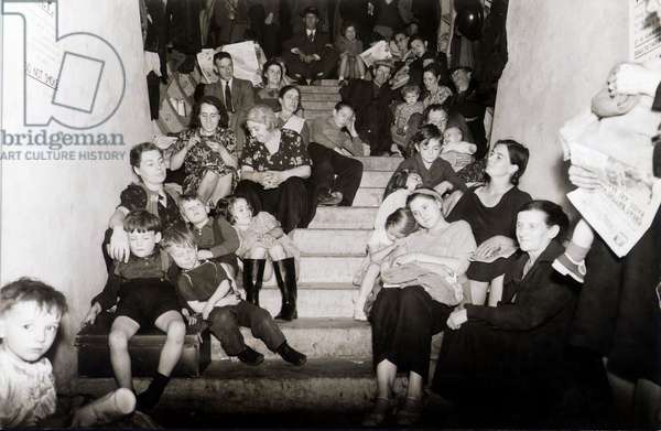 Families take cover from the Luftwaffe bombing of London in a disused London Underground railway tunnel, September 1940 (b/w photo)