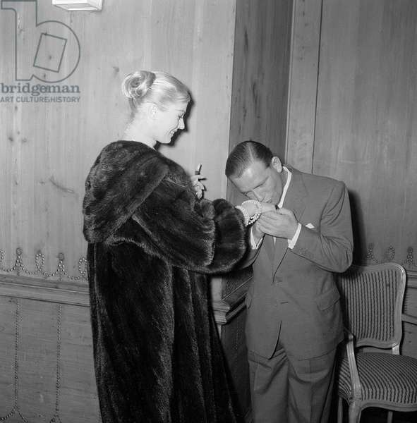 Actor and comedian Norman Wisdom kisses the hand of actress Anita Ekberg at the savoy Hotel, May 1956 (b/w photo)