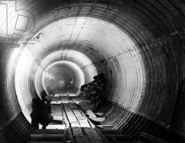 The Tyne Tunnel, runs under the River Tyne from Howdon in North Tyneside to Jarrow in South Tyneside - A view along the pedestrian tunnel at its lowest level, showing the tunnel sections filled with concrete and ready to receive the tiled lining 4 March 1950 (b/w photo)