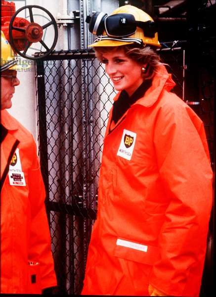 Princess Diana on the north sea oil rig - Diana is wearing a construction hard hat with protective ear guards and an orange over coat, September 1985 (photo)