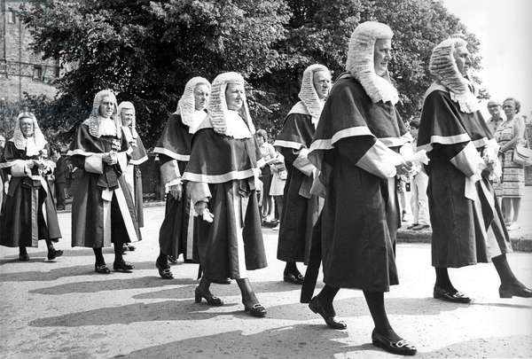 North judges walk in procession across Palace Green wearing their wigs, velvet robes and black stockings as they make their way to Durham Cathedral for their annual service in July 1976 (b/w photo)
