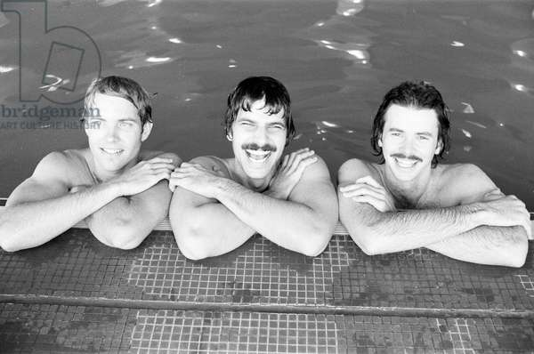 Mark Spitz (centre), USA Olympic Champion, seven x gold medals at the 1972 Munich Olympic Games, pictured with David Wilkie (right), British Olympic Champion, 200 metre breaststroke 1976 Montreal Olympics. Gary Hall (left) USA Olympic Champion, Silver 1968 Mexico City 400 m medley, Silver 1972 Munich 200 m butterfly, Bronze1976 Montreal 100 m butterfly. Photocall ahead of meeting in France to discuss 12 month schedule for Team Arena, pictured together in London, 19th April 1978 (b/w photo)