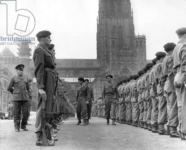 Inspecting officers move through the ranks of soldiers from the Durham Light Infantry T.A. drawn smartly up in from of Durham Cathedral, 1960