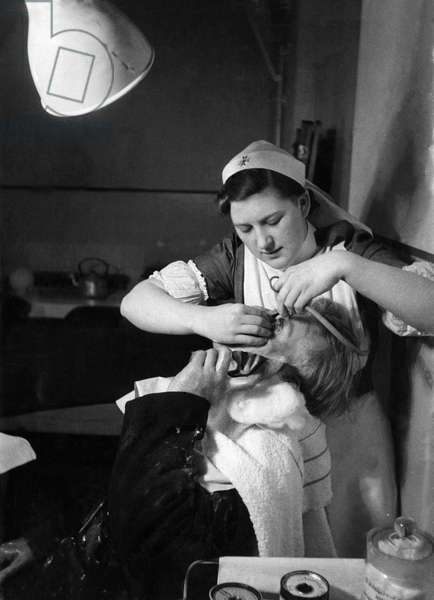 A member of the LFS receiving attention at Westminster Hospital (1st aid post.) during blitz, 20th March 1941 (b/w photo)