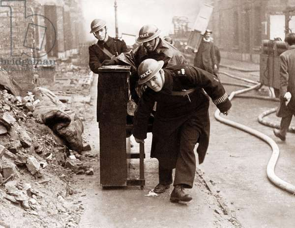 Police remove a piano from a London house threatened by fire during the Blitz (b/w photo)