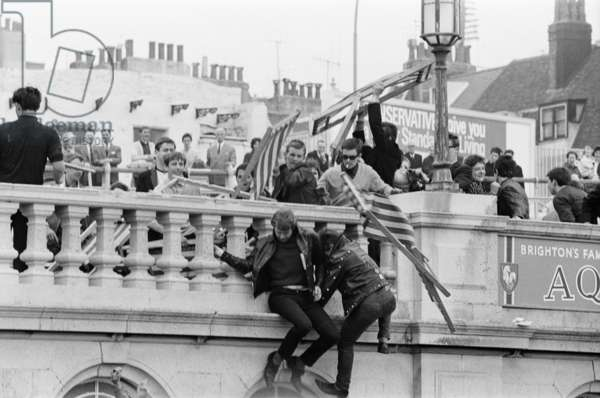 Mods v Rockers - Battle for Brighton, Two rockers cling on to the sides of the building on the beach, as the mods above attempt to throw a deckchair onto them, 18 May 1964 (b/w photo)