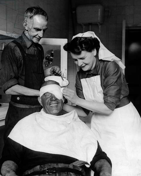 Sister Eira Davies, with help from ambulance man John Price, removes a splinter from Richard Edwards' eye at the new pithead medical centre at Geognant Colliery in Maestag, a model hospital in miniature. Two hundred other collieries are planned to be equipped with centres like this in the next five years.  2nd February 1949