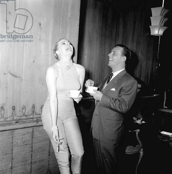 Actor and comedian Norman Wisdom with actress Anita Ekberg at the savoy Hotel in London, May 1956 (b/w photo)