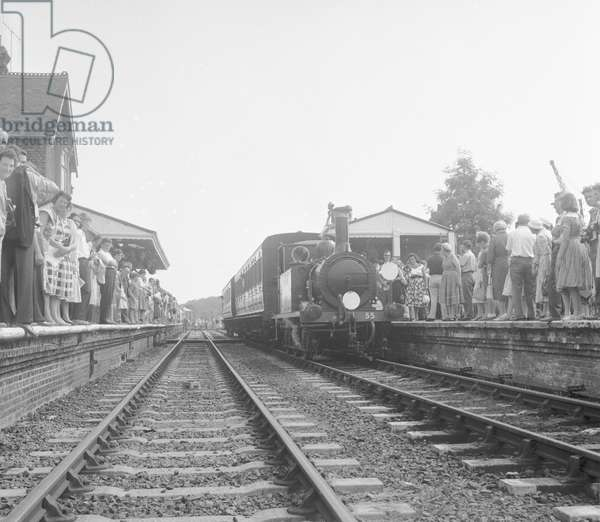 """Crowds on the platform at Horsted Keynes station await the arrival of the London, Brighton & South Coast Railway locomotive No. 55 """"Stepney"""", a Bluebell Line train from Sheffield Park, 8th August 1960 (b/w photo)"""