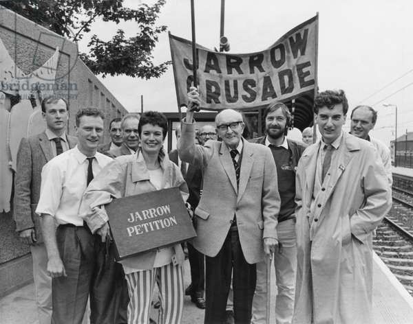 Mr Claude Robinson, one of the original Jarrow marchers, with organisers Simon Osborn (left) and Richard Haswell (right) while Liz Brailsford holds the petition box. Alan Hull from the pop group Lindisfarne is picture to right of Claude. The steps of the historic Jarrow Crusade are to be retraced later this year - in another desperate bid to bring jobs to Tyneside. The modern day hunger marchers are to carry a new petition for work to Downing Street, which pleads for exactly the same as the original did 50 years ago. A new campaign to capture the spirit of the crusade, called Jarrow '86, was officially launched yesterday - with old and new marchers lending the scheme their support. The '86 march will set off from Jarrow on October 5 - exactly 50 years after the first demonstration took to the roads with 200 jobless men. This time, ten people from Jarrow will begin the walk, with others joining from every constituency through which the parade passes, following the original route. 13/08/1986 (b/w photo)