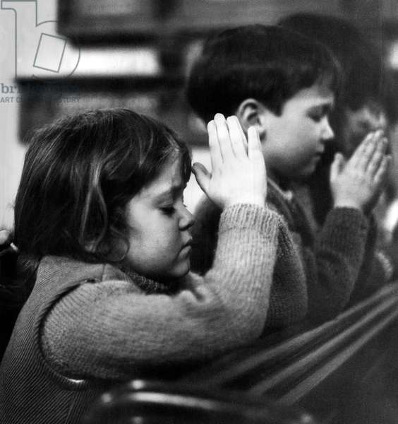 Five year old Jane Curtis praying with her school friends that their village, Stewkley, will be saved after news of the Roskill Commission's Plan for London's third airport was published, 18th December 1970 (b/w photo)