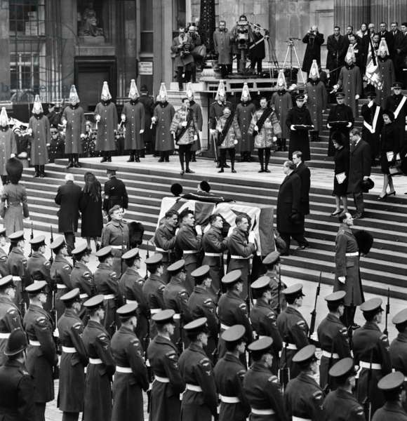 The funeral of Sir Winston Churchill. After the state funeral service in St Paul's Cathedral, the coffin is taken to Bladon Church near his birthplace, Blenheim Palace, Oxfordshire, where Sir Winston will be buried in accordance with his own wish. Pictured, after the funeral service the coffin is loaded onto the gun-carriage at the foot of St Paul's Cathedral steps. 30th January 1965 (b/w photo)