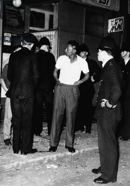 Police speaking to people outside a shop, Bramley Road, 1958 (b/w photo)