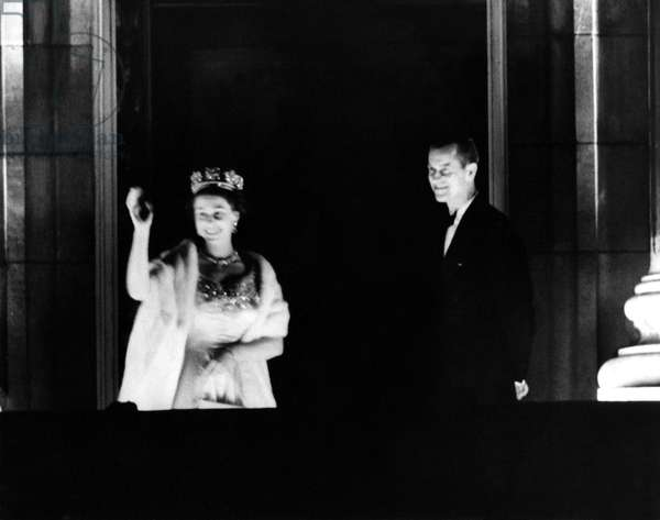 Coronation of Elizabeth II: The Queen and Prince Philip wave to crowds from the floodlit balcony of Buckingham Palace, June 1953 (b/w photo)